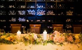 Small wedding reception in the wine cellar of Del Pasto with pastel pink, orange dahlias, roses
