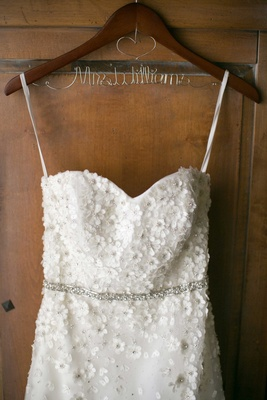 brides wedding dress hanging up on hanger floral details mrs williams