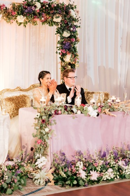 interfaith wedding bride groom on throne settee purple green color palette drift wood air plant