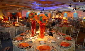 Wedding reception table with colorful centerpieces in tall vases
