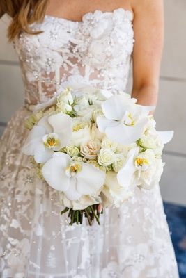 bride in reem acra wedding dress from dimitra's bridal couture with white rose orchid bouquet