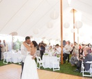 Bride and groom dance under white tent with paper lanterns