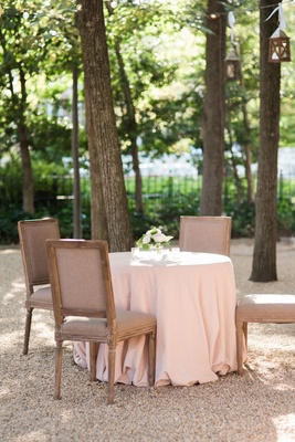 Pink tablecloth with rustic wood and grey taupe chairs by tall trees at Meridian House in Washington