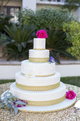 south asian wedding inspiration, ornate white wedding cake with gold border and magenta roses