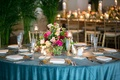 wedding reception in key west with bright blue linens and colorful fall hued flower arrangements