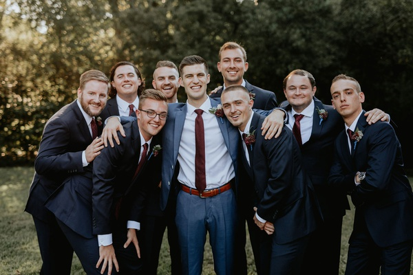 Groom and groomsmen in burgundy ties with matching boutonnieres fall wedding ideas
