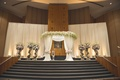Jewish wedding ceremony with white fabric chuppah topped with white flowers, tiebacks at posts