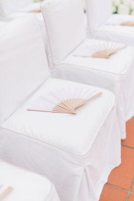 wedding ceremony with chairs with white covers and white fans