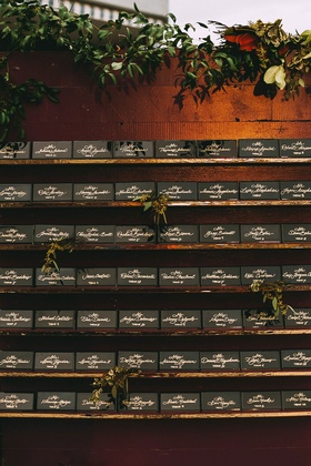 Black tile name plates escort card ideas gold calligraphy on wall with foliage green leaves