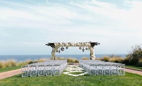 oceanfront wedding ceremony overlooking the pacific ocean wooden arch white flowers mirror balls