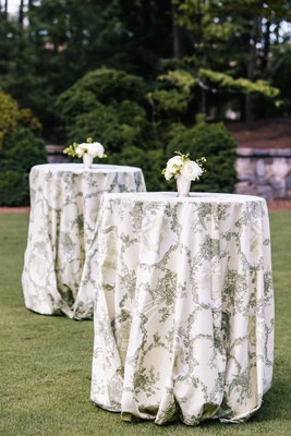 Tall cocktail tables on grass lawn with white and green Southern pattern and small white flowers