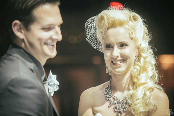Bride at ceremony with chunky necklace and white net veil