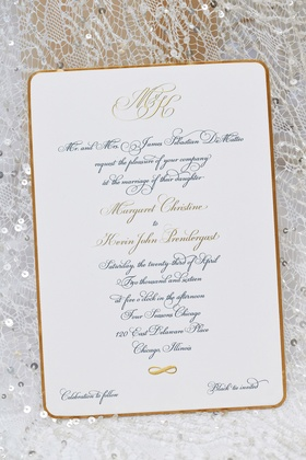 Script calligraphy font with monogram on black tie wedding invitation on top of wedding dress