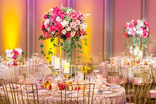 texture linen, pink rose dahlia, greenery centerpiece pillar candles on stands, gold chairs, uplight