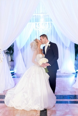 Celebrity fitness trainer bride and groom kiss under wedding drapes