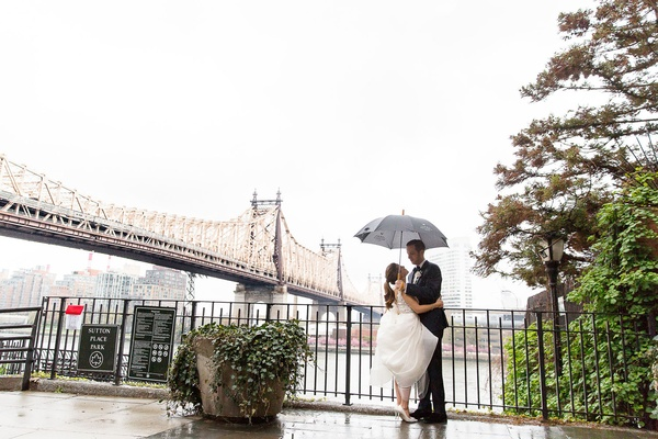 Bride and groom in rain on wedding day umbrella couple portrait Sutton Place Park in New York City