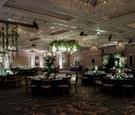 ballroom wedding reception round rectangular tables greenery white flowers candelabra ceiling decor