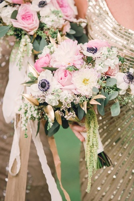 bridesmaid in sequin gold dress holding bouquet of anemone, dahlia, gold leaves, amaranthus pink