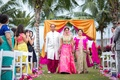 Indian-American bride in pink and turquoise lehenga, walks down the aisle with parents