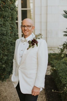 groom in white tuxedo jacket bow tie with large boutonniere burgundy flower greenery statement