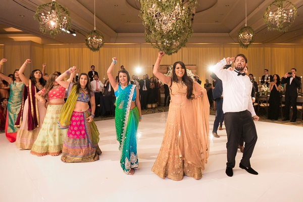 indian wedding bride and groom doing dance performance with friends at reception dance floor