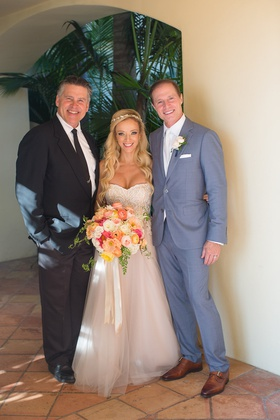 bride in strapless trish peng wedding dress groom in grey suit and reverend clint hufft portrait