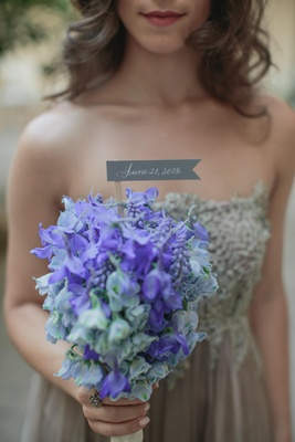 bridesmaid holds bouquet of blue flowers