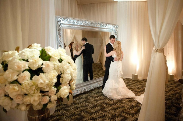 Bride and groom dance in front of mirror at wedding reception