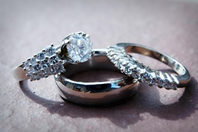 Men's polished wedding band and bride's diamond ring and band