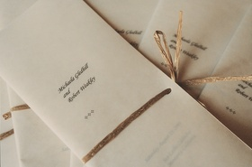 Sheer white booklet tied with raffia ribbon
