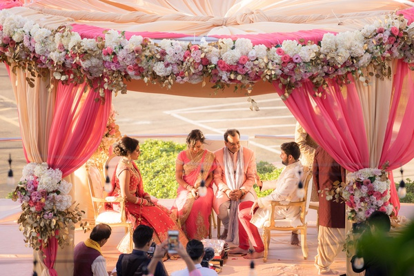 indian wedding outdoor ceremony circular mandap pink gold white flowers peach sunset colors gold