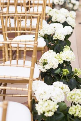 white hydrangeas along aisle next to gold chiavari chairs