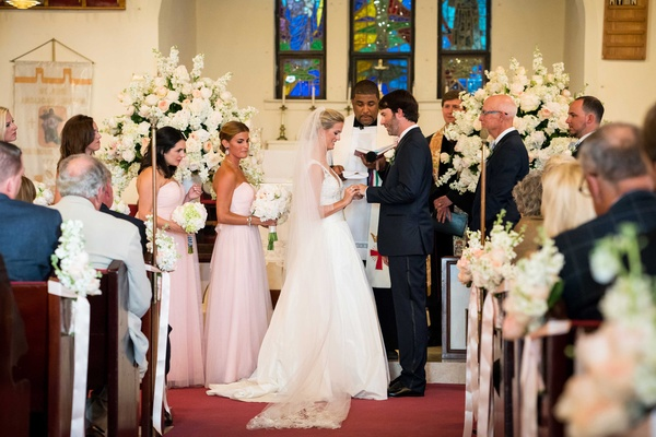Bride in Carolina Herrera dress puts ring on groom at church wedding ceremony in the Bahamas