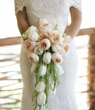 Bride in a lace Anna Maier ~ Ulla-Maija dress and bouquet of pastel orange garden roses, white tulip