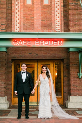 Bride and groom hold hands couple's portrait in front of Cafe Brauer Chicago wedding venue