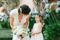 Bride with headpiece and lace wedding dress white bouquet with flower girl in green flower crown