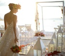 bride walking down aisle beach colorful motif white accents flower crown arch chuppah flowers ocean