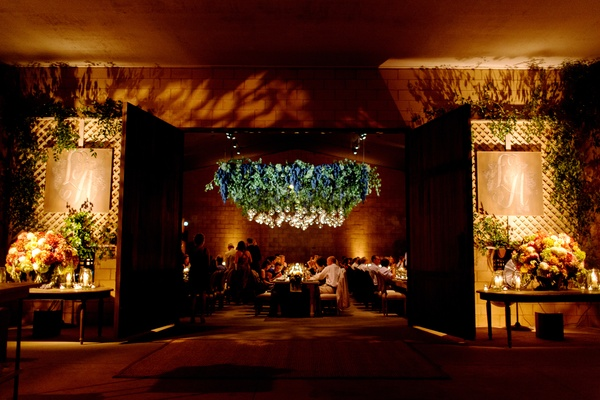Entrance to wine barrel room rehearsal dinner with chandelier