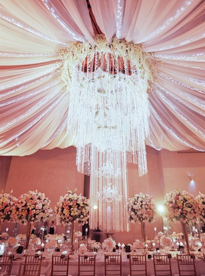 wedding reception drapery over reception table cascading chandelier flower halo embellishments