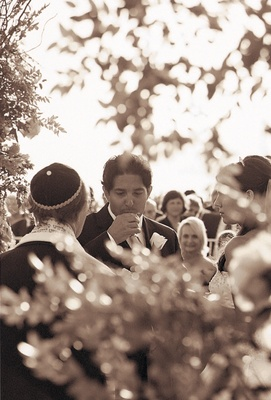 Black and white photo of groom at ceremony
