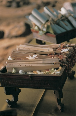 wedding programs and paper fans displayed in wooden boxes