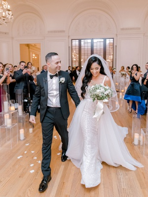 wedding recessional at los angeles ballroom bride in overskirt candles flower petals