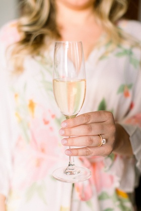 wedding photo of bridesmaid in flower print robe pink with champagne flute gold solitaire ring
