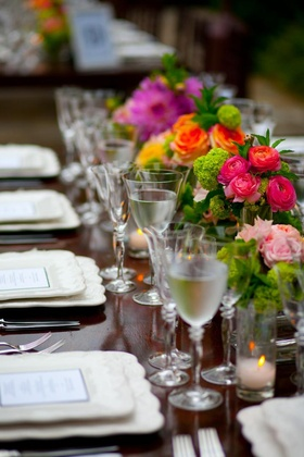 Long reception table with bright pink flowers in vases