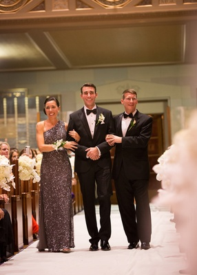 Groom in a black tuxedo walks down the aisle with parents