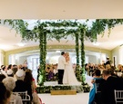 Wedding ceremony jewish service chuppah greenery garland gold step and guests tossing gold confetti