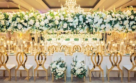 wedding reception gold chairs flower bride groom chairs tall centerpiece chandelier modern gold