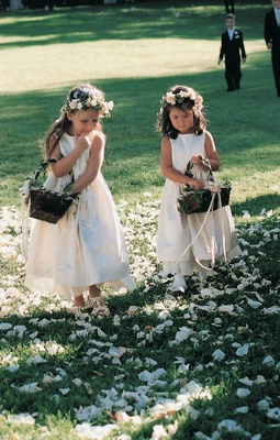 Little girls carrying baskets and wearing flower crowns