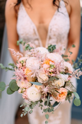 bride with plunging neckline holding bouquet pastel pink and orange pink white ranunculus rose