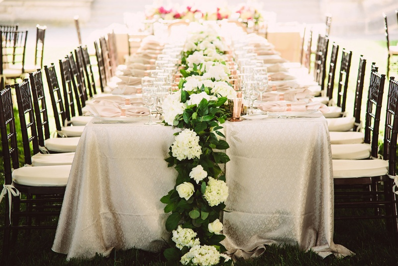 Wedding reception long head table with runner of green garland and white rose hydrangeas rose gold